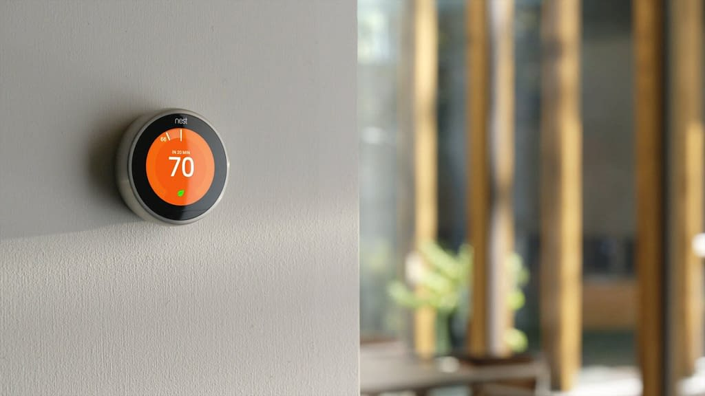 Orange smart thermostat mounted on wall displaying seventy degrees fahrenheit